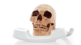 Human skull model with old telephone Stock Photo