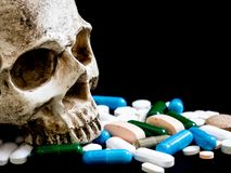 Human skull on multicolored of drug and capsule is on the black background. Close up. We are against drugs anti drugs, cure in c stock image