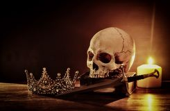 Human skull, old book, sword, crown and burning candle over old wooden table and dark background. Human skull, old book, sword, crown and burning candle over stock photography