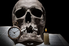 Human skull on old open book with burning candle and vintage clock on black background under beam of light close up.  stock photo