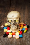 Human skull in the pile of drugs. Human skull in the pile of drugs, sickness and danger Royalty Free Stock Photography