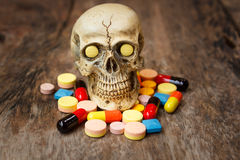 Human skull in the pile of drugs. Human skull in the pile of drugs, sickness and danger Royalty Free Stock Photos