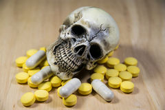 Human skull in the pile of drugs, sickness and danger. The human skull in the pile of drugs, sickness and danger Royalty Free Stock Image