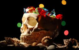 A human skull with precious stones in it. Pirate treasures in the skull royalty free stock photography