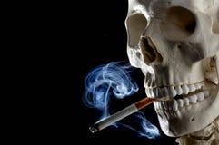Human skull smoking cigarette. Details of human skull smoking lighted cigarette, black background Royalty Free Stock Images