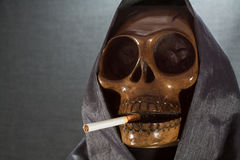 Human skull smoking a cigarette on a black background, Cigarette very dangerous for people. Please don't smoke.Halloween day Royalty Free Stock Image
