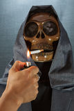 Human skull smoking a cigarette on a black background, Cigarette very dangerous for people. Please don't smoke.Halloween day Stock Image