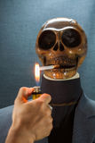 Human skull smoking a cigarette on a black background, Cigarette very dangerous for people. Please don't smoke.Halloween day Stock Photo