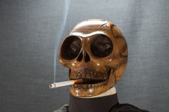 Human skull smoking a cigarette on a black background, Cigarette very dangerous for people. Please don't smoke.Halloween day Royalty Free Stock Photos
