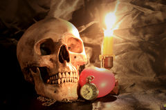 Human skull with vintage pocket clock, red heart and candle light on black fabric background ,Love and time concept in still life. Photography royalty free stock photos