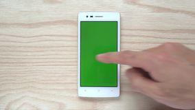 Human slide smartphone or mobile phone green screen on wood background. Human is sliding Smartphone or Mobile Phone green screen on wood background 4k 3840x2160 stock video