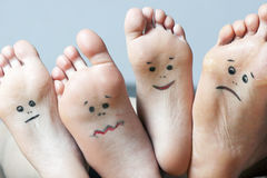 Human soles with painted faces. Close-up. Concept of feet care Stock Images