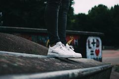 Human Standing on the Ground and Wearing White Nike Sneakers Royalty Free Stock Images