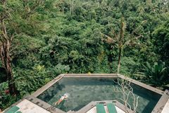 Human swimming in Bali infinity pool royalty free stock images