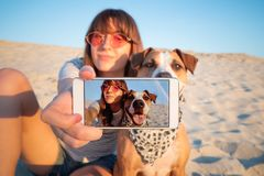 Human taking a selfie with dog. Best friends concept: young female makes self portrait with her puppy outdoors on a beach stock image