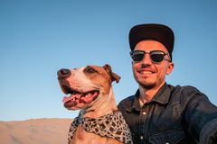 Human taking a selfie with dog on sandy beach. Happy young male. Person makes self portrait with his dog outdoors royalty free stock photo
