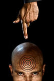 Human target. A men with a target tattooed on his forehead and a hand shooting him Royalty Free Stock Photo