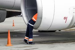 Human technician engineer checks the turbine engine`s airplane blade after the voyage and psodki in the parking at the airport. Stock Photo