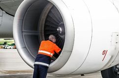 Human technician engineer checks the turbine engine`s airplane blade after the voyage and psodki in the parking at the airport. Human technician engineer checks Stock Photo