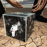Human about to pick up box containing astronaut Stock Photo