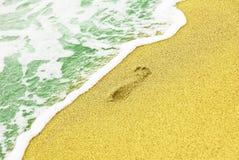 Human trace on sandy beach near azure sea surf. Stock Image
