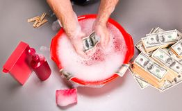Human is washing dollars banknotes in foam Stock Images