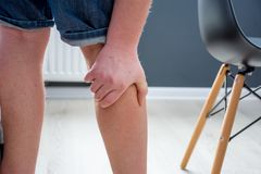 Human, who had been elevated from chair, holding his palm over calf or gastrocnemius muscle, which grabbed cramp with severe pain. Concept images illustrating royalty free stock image