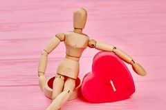 Human wooden dummy and red heart. Wooden dummy mannequin sitting and hugging heart shaped candle. Valentines Day concept stock photos