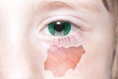 Human& x27; s-Gesicht mit Staatsflagge und Karte von Nigeria Lizenzfreie Stockfotografie