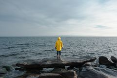 Human in yellow raincoat stand in front of sea. Human in yellow raincoat stand in front of blue sea stock photo