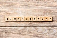 Humanitärt ord som är skriftligt på träsnittet humanitär text på tabellen, begrepp arkivbilder