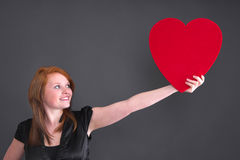 Humanity - girl holding a red heart for love Royalty Free Stock Photography