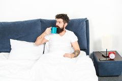 Humanity runs on coffee. Man brutal handsome hipster relaxing bedroom drink coffee. Bearded guy enjoy morning coffee stock images
