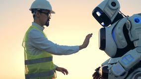 Humano-como el ajuste del robot están siendo regulados por un ingeniero en un casco de protección almacen de metraje de vídeo