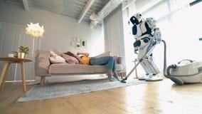 Humano-como el robot está limpiando el cuarto con una mujer que se sienta en un sofá almacen de metraje de vídeo