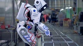 Humano-como el robot está trabajando con un taladro en una unidad de la fábrica almacen de video