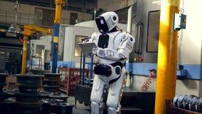 Humano-como el robot está trabajando con una tableta en la fábrica metrajes