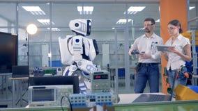 Humano-como el robot está viniendo a los ingenieros que lo controlan remotamente y le dan un taladro metrajes