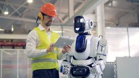 Humano-como el robot está viniendo a un obrero que le esté mostrando algunos gestos almacen de video