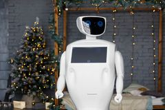 The robot meets Christmas, stands on the background of the garland stock photo
