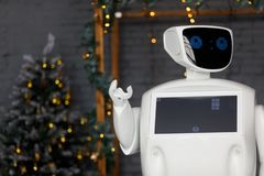 The robot meets Christmas, stands on the background of the garland stock photos