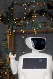Humanoid autonomous robot on the background of Christmas decorations, Christmas tree, bokeh stock photos