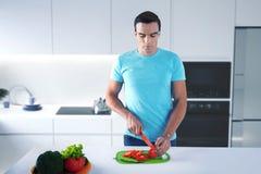 Humanoid futurista que se coloca en la cocina y que corta verduras imagenes de archivo