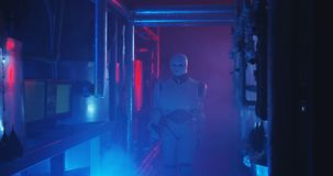 Humanoid robot working in a smoke filled lab. Medium shot of a humanoid robot checking a gauge in a smoke filled lab stock photos