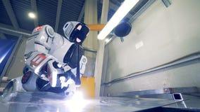 Humanoiden med en svetsningutrustning arbetar på en växt, slut upp lager videofilmer
