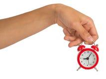 Humans hand holding alarm clock on white Royalty Free Stock Photos