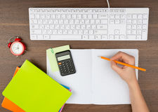 Humans hand writing in copy book with calculator Royalty Free Stock Photos