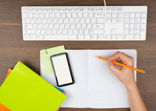 Humans hand writing in copy book with smartphone Stock Photography