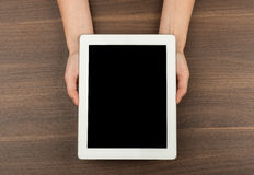 Humans hands holding tablet, top view Royalty Free Stock Photography