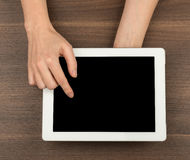 Humans hands pressing on tablet. On wooden table background Royalty Free Stock Images